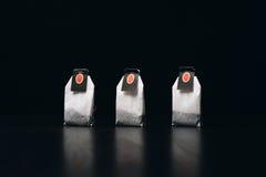 Τσάντες τσαγιού σε μια σκοτεινή στάση υποβάθρου σε μια σειρά Στοκ Φωτογραφία
