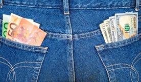 Τσέπες τζιν με τα ευρο- και αμερικανικά τραπεζογραμμάτια Στοκ Εικόνες