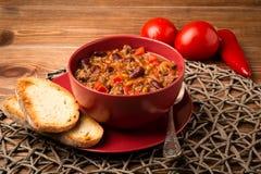 Τσίλι con carne που εξυπηρετείται στο κόκκινο κύπελλο στο ξύλινο υπόβαθρο Στοκ Φωτογραφία
