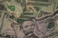 Τσαλακωμένα επάνω χρήματα νομίσματος εγγράφου πέντε δολάρια στο πρώτ στοκ εικόνα