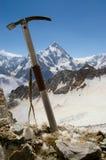 Τσεκούρι πάγου ενάντια στο σκηνικό ενός τοπίου βουνών στοκ φωτογραφίες