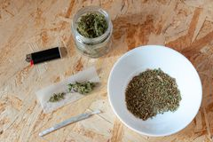 Τσιγάρο μαριχουάνα, που παράγονται με τις κορυφές κάνναβης, κυλώντας έγγραφο και ελαφρύτερη, παράνομη χρήση της ναρκωτικής ουσίας στοκ εικόνες