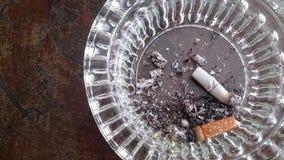 Τσιγάρο στο γυαλί στον ξύλινους πίνακα και τα υπόβαθρα Στοκ εικόνα με δικαίωμα ελεύθερης χρήσης