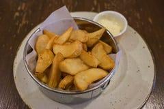 Τσιγαρισμένες σφήνες στο πιάτο ανοξείδωτου με τη σάλτσα ταρτάρου Στοκ εικόνες με δικαίωμα ελεύθερης χρήσης
