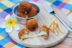 Τσιγαρισμένες σφαίρα και τηγανιτές πατάτες τυριών στο ξύλινο πιάτο Στοκ Εικόνες
