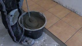 Τσιμέντο κεραμιδιών μιγμάτων χεριών με την εργαλειομηχανή στην κουζίνα απόθεμα βίντεο