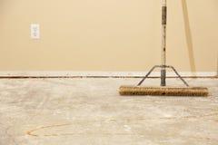 Τσιμεντένιο πάτωμα σπιτιών με τη σκούπα έτοιμη για την εγκατάσταση δαπέδων Στοκ φωτογραφία με δικαίωμα ελεύθερης χρήσης