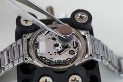 Τσιμπιδάκια με την μπαταρία και Wristwatch Στοκ Φωτογραφία