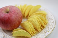 Τσιπ πατατών και κόκκινο μήλο στο πιάτο Διατροφή, πάχυνση στοκ φωτογραφία με δικαίωμα ελεύθερης χρήσης