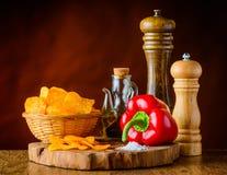 Τσιπ πατατών, κόκκινο πιπέρι και συστατικά Στοκ Φωτογραφίες