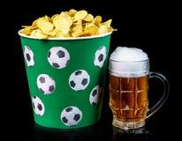 Τσιπ πατατών σε έναν κλασικό κάδο και ένα ποτήρι της μπύρας που απομονώνεται σε ένα μαύρο υπόβαθρο Στοκ Φωτογραφίες