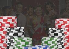 Τσιπ χαρτοπαικτικών λεσχών πόκερ μπροστά από τους παίζοντας ανθρώπους στοκ φωτογραφίες
