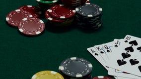 Τσιπ χαρτοπαικτικών λεσχών και κάρτες πόκερ στον πράσινο πίνακα απόθεμα βίντεο