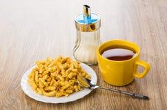 Τσοκ-τσοκ με το σουσάμι στο πιάτο, τσάι, κουταλάκι του γλυκού, κύπελλο ζάχαρης Στοκ Φωτογραφίες