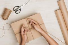 Τυλίγοντας δώρο ατόμων Ένα δέμα που τυλίγεται έγγραφο και που δένεται στο καφετί με Στοκ εικόνες με δικαίωμα ελεύθερης χρήσης