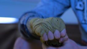 Τυλίγοντας επίδεσμοι μπόξερ σε ετοιμότητα του πριν από την πάλη κλείστε επάνω Το άτομο δένει τα χέρια του με έναν επίδεσμο Στοκ εικόνα με δικαίωμα ελεύθερης χρήσης
