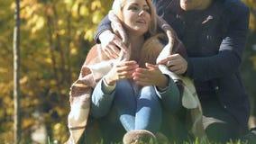 Τυλίγοντας φίλη τύπων με το κάλυμμα στο πάρκο, κρύα ημέρα φθινοπώρου, σχέσεις φροντίδας απόθεμα βίντεο