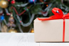 Τυλιγμένα δώρα με την κόκκινη κορδέλλα στον άσπρο πίνακα στοκ φωτογραφίες