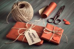 Τυλιγμένο δώρο με τον ευτυχή βαλεντίνο ` ετικεττών `, το καφετί σκοινί, το τυλίγοντας έγγραφο, το ψαλίδι και τις διακοσμητικές κα Στοκ Φωτογραφίες