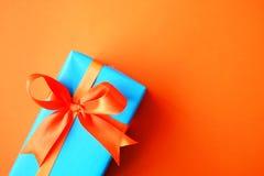 Τυλιγμένο παρόν κιβώτιο στο πορτοκαλί φωτεινό υπόβαθρο Έννοια διακοπών στοκ φωτογραφίες