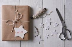Τυλιγμένο χριστουγεννιάτικο δώρο με μια ετικέττα που σφραγίζεται με εύθυμο Στοκ εικόνα με δικαίωμα ελεύθερης χρήσης
