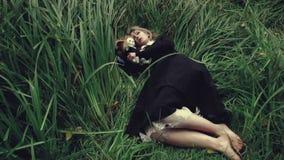 Τυποποιημένη βλασταημένη ανατριχιαστική λευκιά αντιμέτωπη γυναίκα με μια κούκλα στη χλόη στην τοποθέτηση ξύλων απόθεμα βίντεο