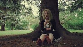 Τυποποιημένη βλασταημένη ανατριχιαστική λευκιά αντιμέτωπη γυναίκα με μια κούκλα στη χλόη στα ξύλα φιλμ μικρού μήκους