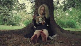 Τυποποιημένη βλασταημένη ανατριχιαστική λευκιά αντιμέτωπη γυναίκα με μια κούκλα στη χλόη στα ξύλα απόθεμα βίντεο