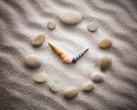 Τυποποιημένο ρολόι πινάκων για τα κοχύλια στην άμμο για τη συγκέντρωση και τη χαλάρωση για την αρμονία και την ισορροπία στην καθ Στοκ Φωτογραφίες