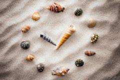 Τυποποιημένο ρολόι πινάκων για τα κοχύλια στην άμμο για τη συγκέντρωση και τη χαλάρωση για την αρμονία και την ισορροπία στην καθ Στοκ Εικόνα