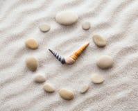 Τυποποιημένο ρολόι πινάκων για τα κοχύλια στην άμμο για τη συγκέντρωση και τη χαλάρωση για την αρμονία και την ισορροπία στην καθ Στοκ Εικόνες