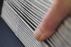 Τυπωμένες εφημερίδες που φυλλομετρούνται κατευθείαν από τον αναγνώστη στοκ φωτογραφία