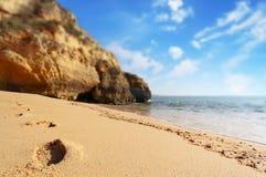 Τυπωμένες ύλες ποδιών στην παραλία στο ηλιοβασίλεμα, Λάγκος, Πορτογαλία Αντίθετο φως Στοκ φωτογραφία με δικαίωμα ελεύθερης χρήσης