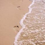 Τυπωμένες ύλες ποδιών στην ωκεάνια άμμο παραλιών Στοκ Εικόνα