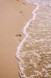 Τυπωμένες ύλες ποδιών στην ωκεάνια άμμο παραλιών Στοκ εικόνα με δικαίωμα ελεύθερης χρήσης