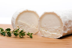 Τυρί αιγών με το θυμάρι σε έναν ξύλινο τέμνοντα πίνακα Στοκ Φωτογραφίες