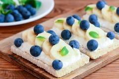Τυρί εξοχικών σπιτιών, μπανάνες και σάντουιτς μούρων Σάντουιτς διατροφής με το παξιμάδι στον ξύλινο πίνακα closeup Στοκ Εικόνα