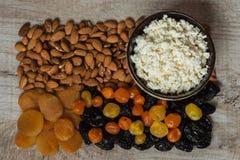 Τυρί εξοχικών σπιτιών στο άσπρο πιάτο Δαμάσκηνα, ξηρά βερίκοκα, ξηρά μανταρίνια και αμύγδαλα σε ένα ελαφρύ ξύλινο υπόβαθρο Στοκ Εικόνες