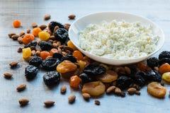 Τυρί εξοχικών σπιτιών στο άσπρο πιάτο Δαμάσκηνα, ξηρά βερίκοκα, ξηρά μανταρίνια και αμύγδαλα σε ένα ελαφρύ ξύλινο υπόβαθρο Στοκ εικόνα με δικαίωμα ελεύθερης χρήσης