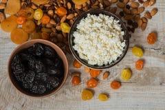 Τυρί εξοχικών σπιτιών στο άσπρο πιάτο και τα δαμάσκηνα στο καφετί πιάτο Δαμάσκηνα, ξηρά βερίκοκα, ξηρά μανταρίνια και αμύγδαλα σε Στοκ Εικόνες