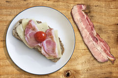 Τυρί ζαμπόν και σάντουιτς ντοματών με τη φέτα από χοιρομέρι μπέϊκον στο ξύλο Στοκ φωτογραφία με δικαίωμα ελεύθερης χρήσης