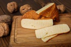 Τυρί και καρύδια στον τέμνοντα πίνακα Στοκ Φωτογραφίες
