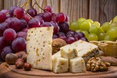Τυρί και σταφύλια στο ξύλινο υπόβαθρο Στοκ εικόνες με δικαίωμα ελεύθερης χρήσης