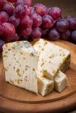 Τυρί και σταφύλια στο ξύλινο υπόβαθρο Στοκ Εικόνα