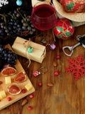Τυρί και σύκα σε έναν ξύλινο πίνακα, κόκκινο κρασί στις ιδιότητες ενός γυαλιού, σταφυλιών και Χριστουγέννων γύρω Στοκ Εικόνες