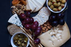 Τυρί, κροτίδα, σταφύλι, καρύδια σε ένα μαύρο υπόβαθρο Στοκ Φωτογραφίες