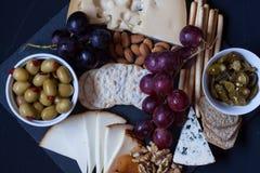 Τυρί, κροτίδα, σταφύλι, καρύδια σε ένα μαύρο υπόβαθρο Στοκ φωτογραφία με δικαίωμα ελεύθερης χρήσης