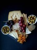 Τυρί, κροτίδα, σταφύλι, καρύδια σε ένα μαύρο υπόβαθρο Στοκ εικόνες με δικαίωμα ελεύθερης χρήσης