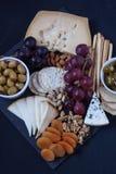 Τυρί, κροτίδα, σταφύλι, καρύδια σε ένα μαύρο υπόβαθρο Στοκ φωτογραφίες με δικαίωμα ελεύθερης χρήσης