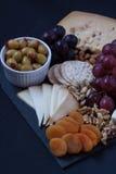 Τυρί, κροτίδες, σταφύλι, καρύδια σε ένα μαύρο υπόβαθρο Στοκ Φωτογραφία
